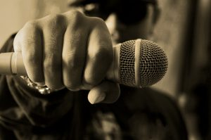 masculine hand with microphone held in it